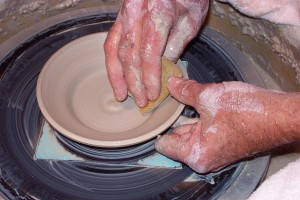 Hands making pottery.